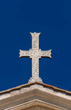 Ancient Holy cross with relief against blue sky, at the top of Saints Boniface and Alexius in Rome