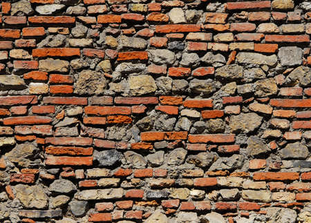 Composite old stone and bricks wall with rough surface as background