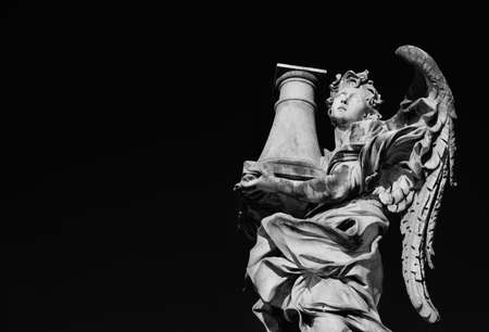 Angel statue holding the Column of Jesus Passion looks at the Heaven A 17th century baroque masterpiece at the top of Sant'Angelo Bridge in the center of Rome (Black and White with copy space)