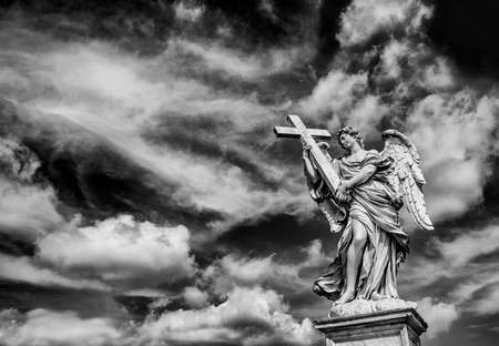 Angel holding the Holy Cross with heavenly sky and copy space. A 17th centuty baroque masterpiece at the top of SantAngelo Bridge in the center of Rome (Black and White)
