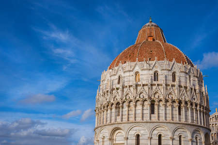 Pisa Baptistry gothic medieval dome among clouds just before sunset