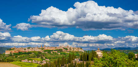 View of Orvieto medieval historic center with its characteristic ancient buildings made of tuff stone, beautiful clouds above and the Umbria green countryside