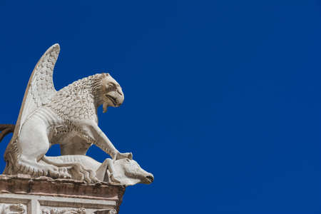 Griffon symbol of the city of Perugia in Umbria. Ancient 14th century medieval marble statue of the mythical beast against blue sky (with copy space)