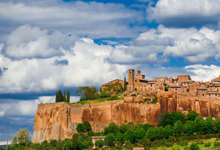 View of Orvieto medieval historic center with its characteristic ancient buildings made of tuff stone and beautiful clouds above