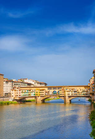 View of the famous Ponte Vecchio (Old Bridge) over River Arno in the historic center of Florence (with copy space above)