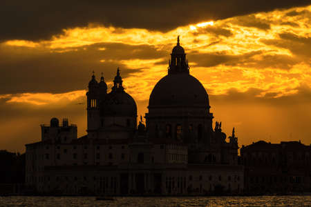 Mysterious and beautiufl sunset over Salute Basilica (Saint Mary of Health) old domes in Venice