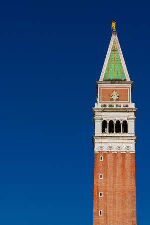 Saint Mark bell tower in the center of Venice with golden angel statue at the top (with copy space)