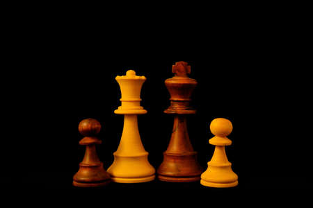 Black King, White Queen and Pawn as mixed family concept.Standard chess wooden pieces on black background