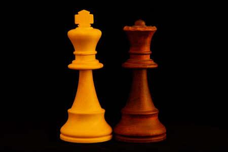 Le roi blanc, la reine noire comme concept de couple mixte. Pièces en bois d'échecs standard sur fond noir