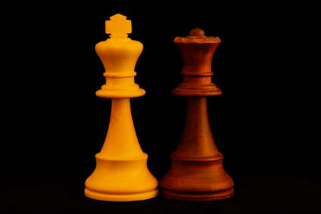 White King, Black Queen as mixed couple concept.Standard chess wooden pieces on black background 스톡 콘텐츠