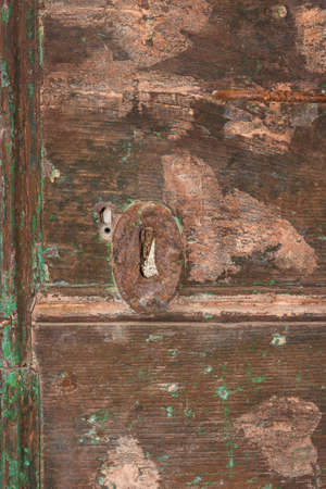 Iron keyhole with rust on an old wooden door