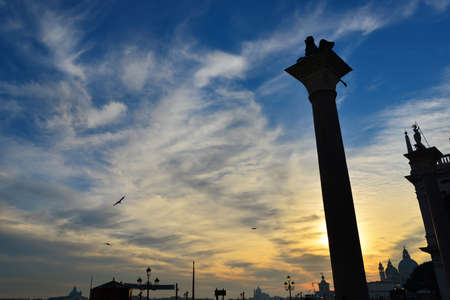Beautiful sunset sky over Venice monuments and Saint Mark basin 免版税图像