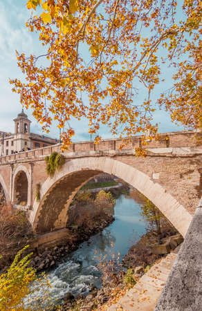 Autumn and foliage in Rome. View of  Pons Fabricius with autumnal leavs and Tiber River, built in 62 BC, its one of the oldest ancient roman bridge still in use