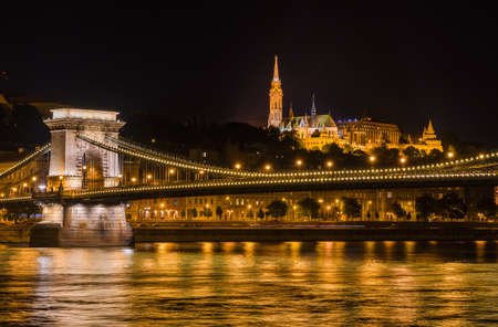 Budapest by night. View of Danube in the center of Budapest with the iconic and monumental Chain Bridge, St Matthias Church and Fishermans Bastion at the top of Castle Hill