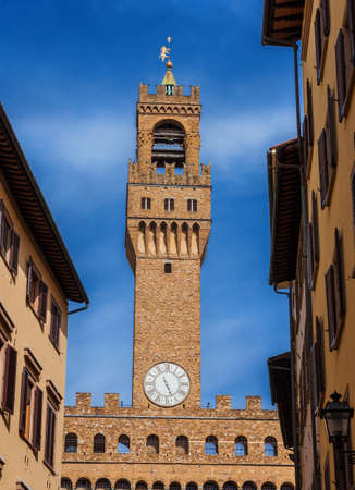 Palazzo Vecchio (Old Palace) clocktower, the beautiful Florence town hall erected in the 14th century and  designed by the famous medieval architect Arnolfo di Cambio, seen from a narrow street in the city historic center