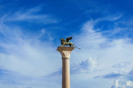 Saint Mark Winged Lion medieval statue, a symbol of the Old Venice Republic, at the top of an ancient column among clouds Archivio Fotografico