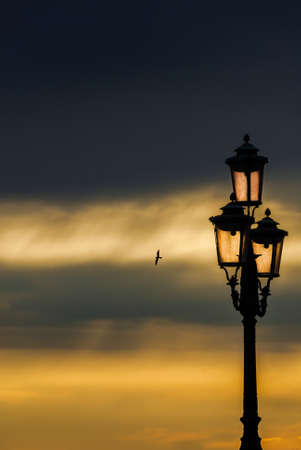 Old traditional Venice street lamp at sunset in a romantic and unique atmosphere (with copy space)