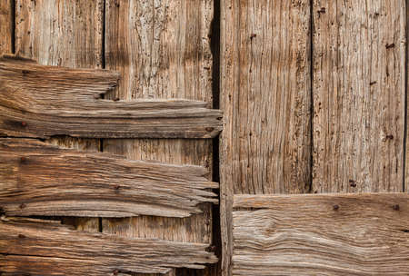 Old wooden boards with iron nails, holes and worn varnish background