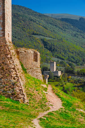 Assisi ancient medieval walls ruins at the top of the town among woods Banco de Imagens