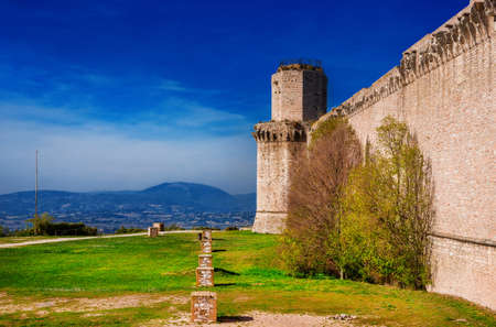 Assisi ancient medieval walls ruins at the top of the town with Umbria countryside view