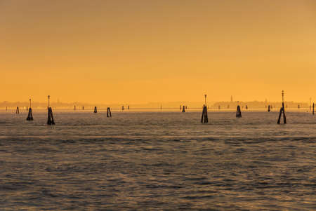Misty view of Venice Lagoon under winter sunset light with islands in the distance as background Banco de Imagens - 138573532