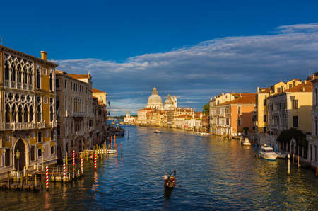 View of the famous Salute Basilica (St Mary of Health) baroque dome with Grand Canal and gondola from Academy Bridge in Venice Banco de Imagens