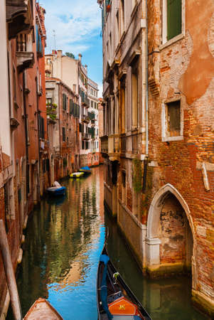 View of a characteristic Venice narrow canal with gondola and old traditional houses in the Castello District Banco de Imagens - 138573734