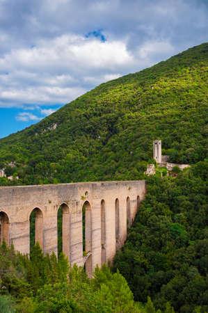 Ancient medieval Ponte delle Torri (Tower Bridge) ruins in Spoleto among woods Banco de Imagens - 138573739