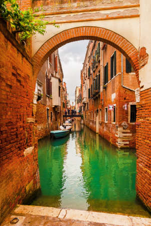 View of a characteristic Venice canal and old traditional houses through a brick arch in the quiet Santa Croce District Banco de Imagens - 139641173