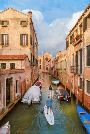 Stand up paddleboarding in Venice. Tourists explore the characteristic venetian canals in the quiet Cannareggio District with Madonna dellOrto Church in the background