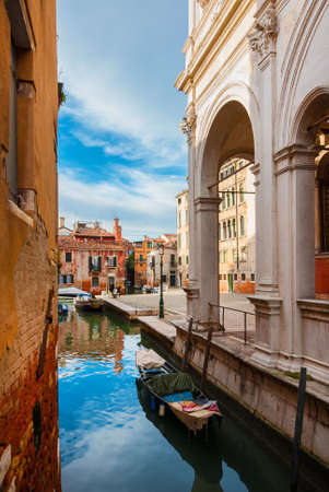 View of Rio della Frescada canal and Castelfrote area with its colorful houses just behind the famous Scuola Grande di San Rocco (Great School of St Roch) in Venice