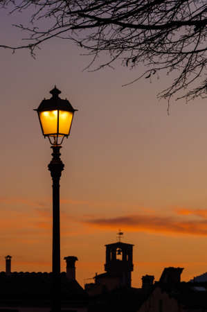 Evening in Lucca with old street lamp and medieval Torre delle Ore, the city ancient clock tower Banco de Imagens