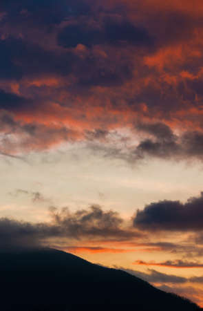 Orange and purple sunset clouds above a mountain as background
