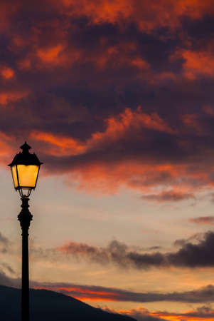 Old fashioned street lamp against beautiful sunset sky and colorful clouds (with copy space)
