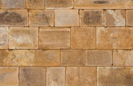 Old brownish stone block wall as background
