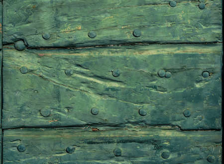 Old wooden doorl with green varnish, cracks and iron studa as background