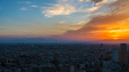 Sunset view of city endless suburbs of Meguro, Setagaya and Kawasaki with the  iconic Mount Fuji wrapped in evening mist, from Ebisu