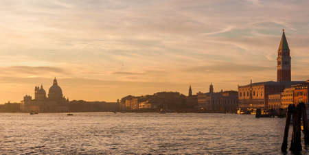 Venice Lagoon with St Mark Square famous monument, Salute Basilica dome and beautiful sunset colors and evening haze