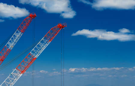 Construction industry and development. Two cranes at work among clouds (with copy space) 版權商用圖片
