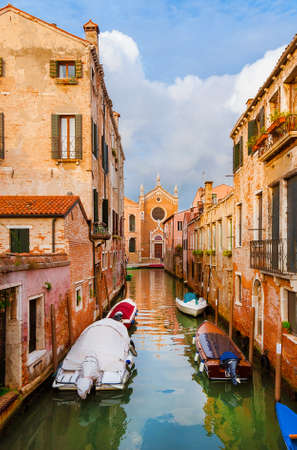 View of Rio Ca brazzo, a characteristic Venice canal with old traditional houses and Church of the Madonna dell'Orto at the end, in the quiet Cannareggio District