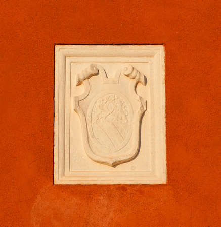 Old heraldic emblem with a damaged relief on a Venice red plaster wall 新聞圖片