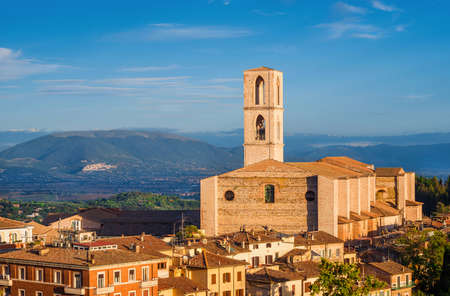 View Perugia huge and iconic St Dominic Basilica and Umbria countryside with the famous medieval city of Assisi in the background at sunset