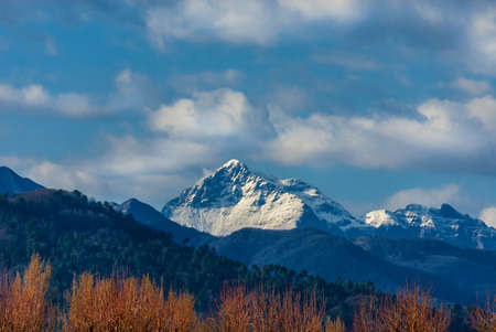 Mountains, woods and clouds above. View of Apennine with snow