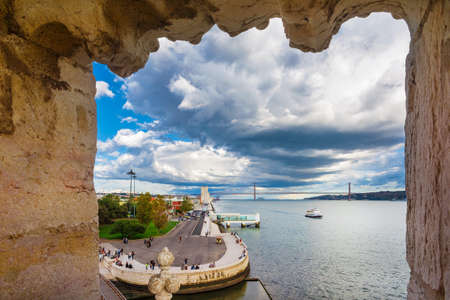 View of the famous Pradao dos Descrobrimentos, 25 de Abril Bridge and River Tagus with stormy clouds from Belem Tower
