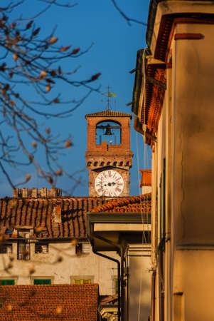 View of Lucca historic center with medieval and iconic 'Torre delle Ore'' (Clock Tower), a city landmark, rises above the city old roofs