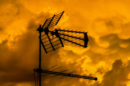 TV antennas and arrays with golden sunset sky and clouds