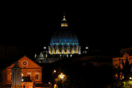 Night in Rome. View of the iconic St Peter dome illuminated, in the city historic center Редакционное