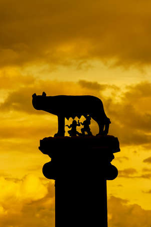 The dawn of the Roman Empire. The legendary Capitoline Wolf with royal twins at the top of Capitol Hill in Rome, against golden sky Редакционное