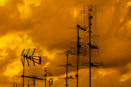 Different kinds of TV antennas and arrays with golden sunset sky and clouds Фото со стока