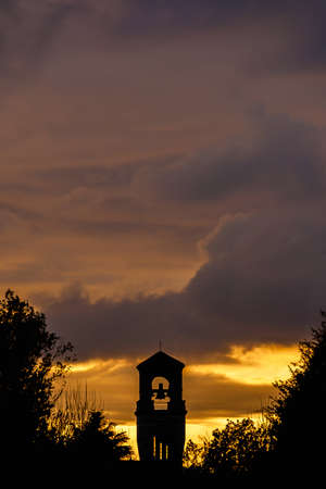 Beautiful sunset clouds over an old bell tower (with copy space above)